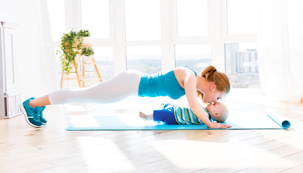 SuperMama - Eine Mama macht Liegestütze und kuesst dabei ihr Baby