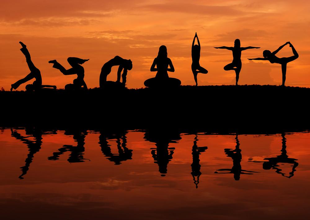 Eine Gruppe Menschen macht im Sonnenuntergang Yogaposen, Bodyart