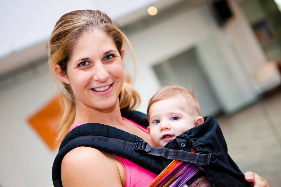 Frau mit Baby in Trage