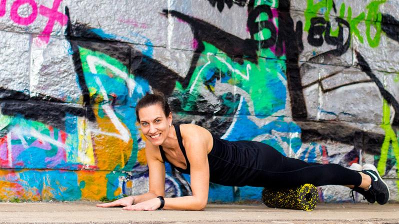 Yoga Trainerin macht Yoga mit der Faszienrolle