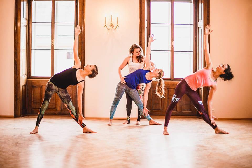 Yogatrainerin zeigt ihren Schülerinnen die richtige Haltung