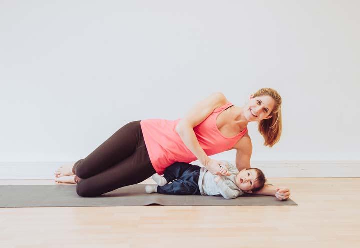 Trainerin mit Baby beim Yoga