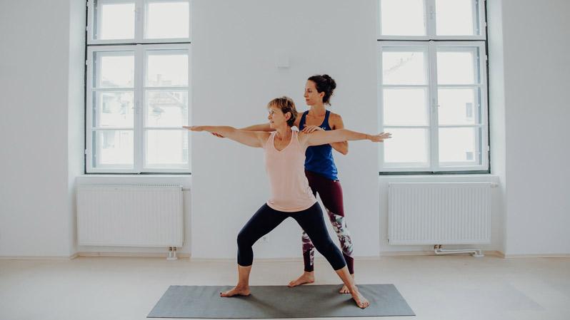 Yogatrainerin zeigt Yogaanfängerin die richtige Körperhaltung im Superactive Studio